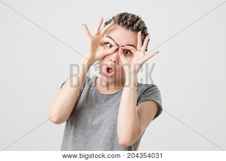 Portrait of funny caucasian girl. She made positive grimace with hands. Positive facial expression