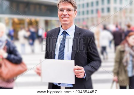businessman in the street, holding blank sign