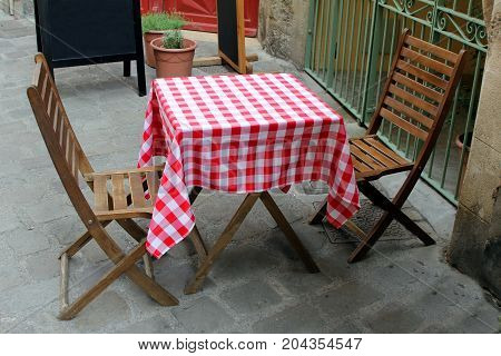 Wooden Table And Chairs In A Street Cafe Outside, With Red Gingham Table Cloth. Blank Blackboard In