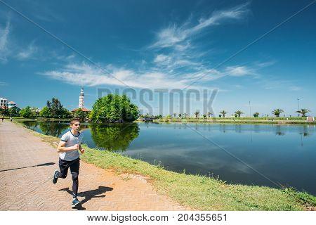 Batumi, Adjara, Georgia - May 25, 2016: Man athlete jogging on a summer sunny day near Ardagani Lake In Batumi, Adjara, Georgia.