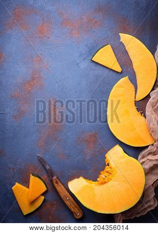 Raw chopped pumpkin on concrete background. Top view
