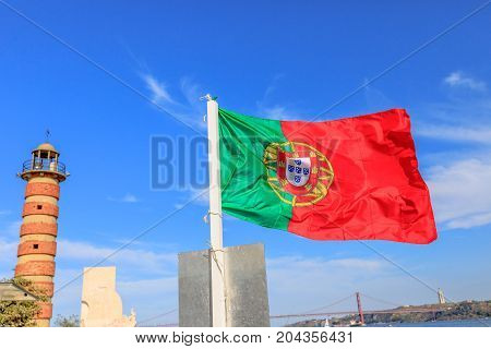 Symbols and icons in Lisbon city: Belem Lighthouse, flag of Portugal waving, Discoveries Monument, Bridge of 25 April and Tagus river. Belem District, Lisbon, Portugal, Europe.