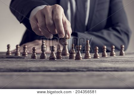Retro Style Image Of A Businessman Playing A Game Of Chess On An Old Wooden Table