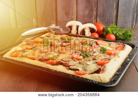 Pizza At Home With Some Ingredients And Special Knife Over Wooden Background