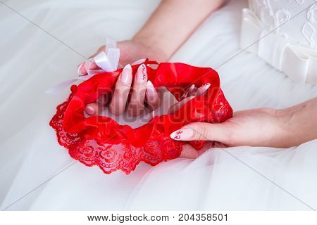 The bride holds the red garter in the white Studio.