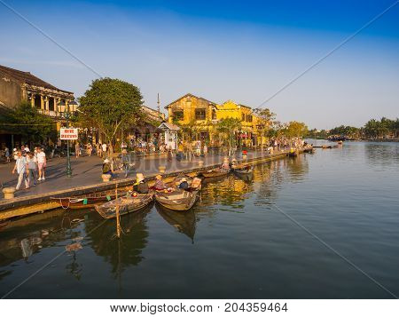 HOIAN, VIETNAM, SEPTEMBER, 04 2017: Traditional boats in front of ancient architecture in Hoi An, Vietnam. Hoi An is the World's Cultural heritage site, famous for mixed cultures architecture.