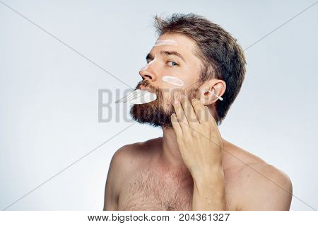 Young guy on white isolated background, cream, cotton pads, ear wand.