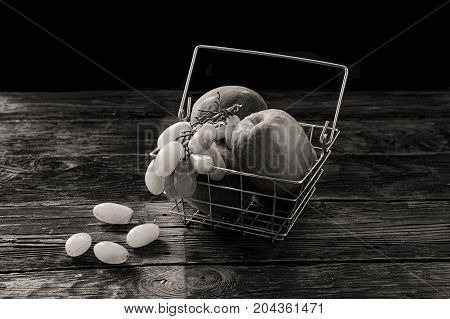 A B&W image of grapes and apples in a wire basket.