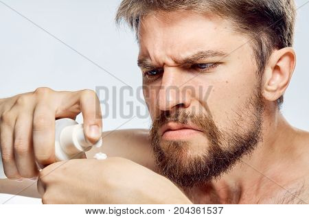 Man with a beard on a light background applies cosmetic cream, portrait, emotions.