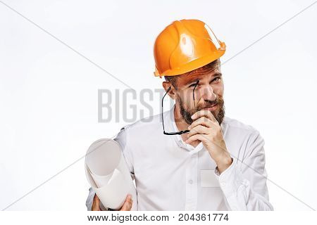 Engineer with a beard on a white isolated background holds drawings.