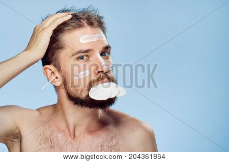 Young guy on a blue background, cream, cotton wool, ear wand.