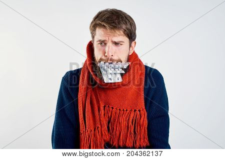 A man with a beard on a light background holds a pill in his mouth, fight, flu, sick.