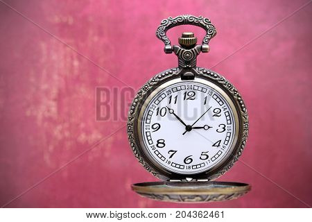 old pocket watch on grunge red wall background