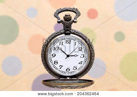 old pocket watch on polka dot pattern background