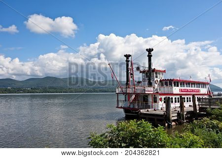 NEWBURGH NEW YORK - SEPTEMBER 15 2017. The River Rose cruise boat sits docked on the Hudson River in Newburgh New York under blue skies with white clouds and Mt. Beacon in the background.