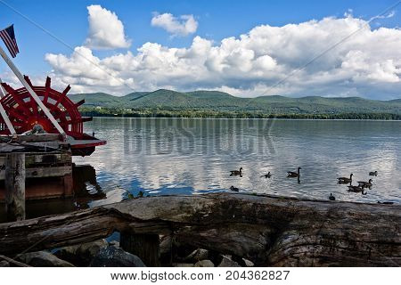 A view of the scenic Hudson River from Newburgh New York Orange County. Mount Beacon proivdes the backdrop for the river where ducks are swimming and the red wheel of a river boat is visible on the left.