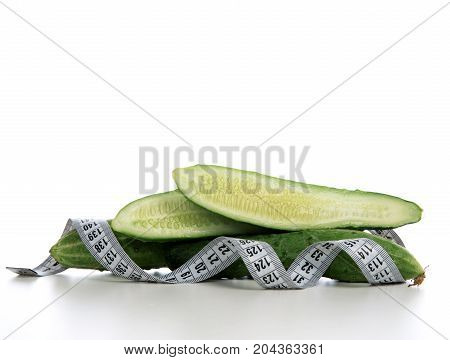 Diet weight loss breakfast concept with tape measure organic green cucumbers isolated on a white background
