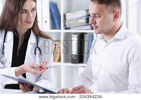 Female Doctor Hand Hold Silver Pen And Showing Pad