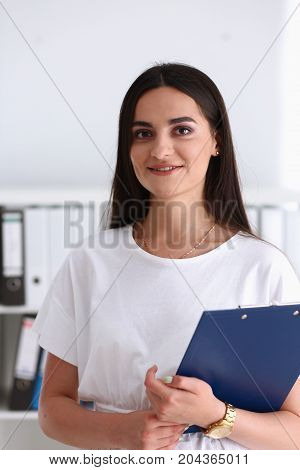 Indian Woman Holding Clipboard In Hand Smiling And Looking At Camera