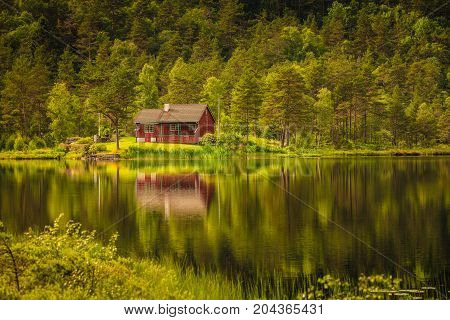 Wooden Cabin In Forest On Lake Shore, Norway