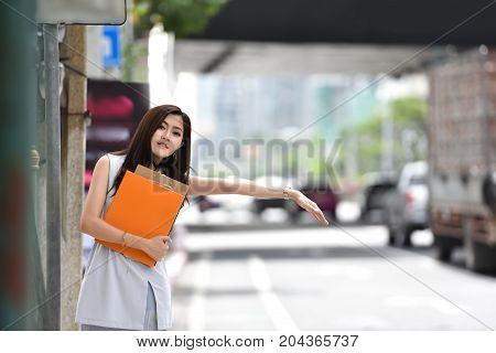 Asian Business woman hailing cab. Beautiful female is calling a taxi in a city. copy space.