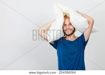 Sleeping well concept. Happy young man rested after good night sleep playing with pillows smiling having fun