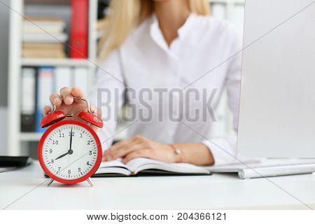 Female Hand On The Alarm Clock A Red Color