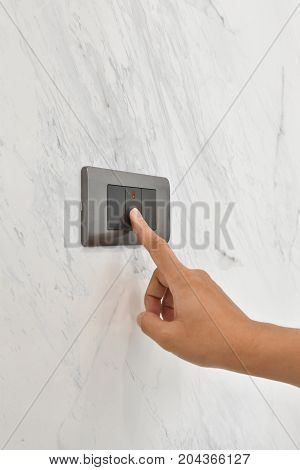 Close up hand turning on or off on grey light switch with white marble background. Copy space.