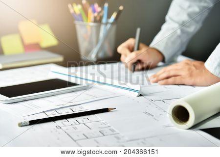 Blurred Designer Man working with sketching on Interior Architecture blueprint. Office supplies equipment.