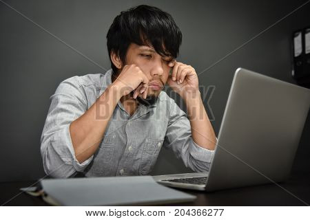 Sleepy Tired Asian businessman working with laptop on grey background. Overtime working.