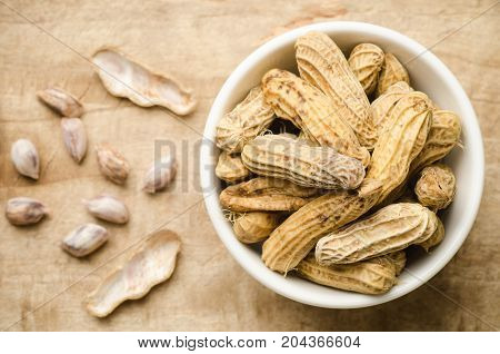 Boiled peanuts or groundnuts in a bowl and peeled peanuts on wooden background for eating
