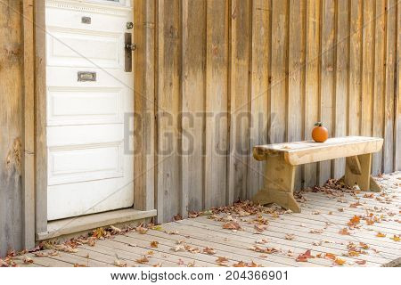 Rustic Simple Wood Porch And Painted White Door, Small Orange Pumpkin Sitting On Bench