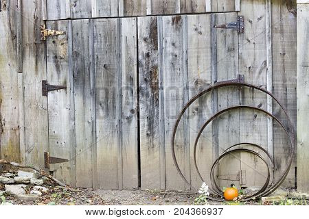 Small Pumpkin In Front Of Vintage Rustic Farm Garage Doors With Iron Parts And Weathered Wood