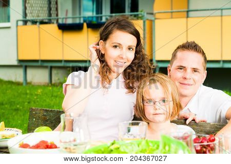 a family are having a picnic in the garden