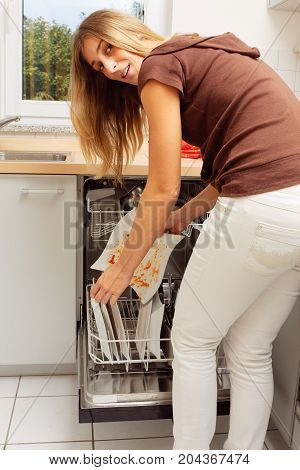 a young woman is putting dirty plates into the dishwasher