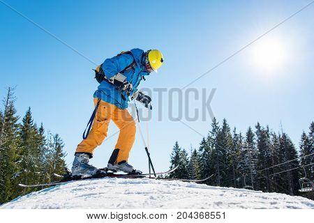 Low Angle Shot Of A Skier Wearing Riding Equipment Standing On Top Of The Hill In The Mountains At S