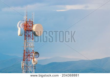 telecommunication tower with mountain range background with warm sunset light casting on clouds good background for wireless technology or telecommunication concept with room for text or copy space