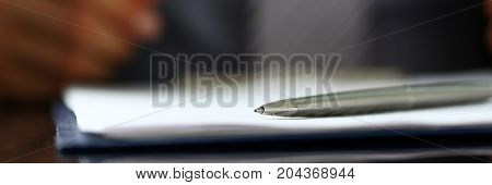 Silver Pen Lying On Form Clipped To Pad Closeup