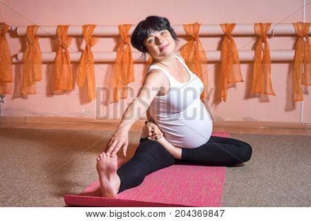 Pregnancy Yoga and Fitness concept. Healthy maternity lifestyle concept. 40 week pregnant middle aged caucasian woman sitting doing yoga exercises twisting.