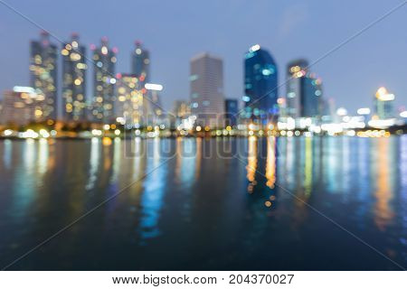 Blue twilight office building blurred light water front abstract background