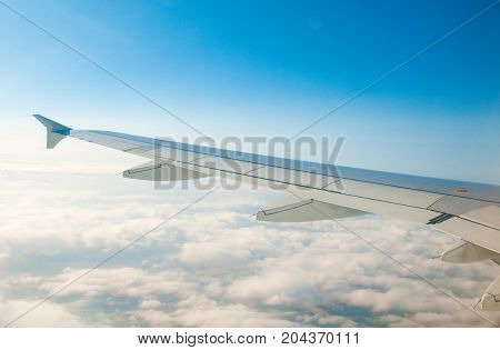The wing of an airplane in the sky above the clouds