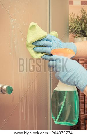 Hand Of Senior Woman Cleaning Shower Using Green Microfiber Cloth And Detergent, Household Duties Co