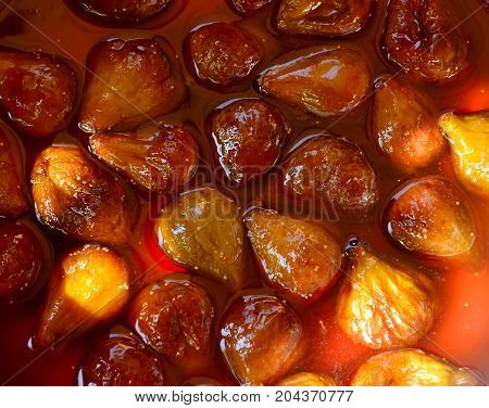 Fig jam or jelly cooking process. Brilliant figs in syrup, close-up. The fig jam is boiling, shiny berries in liquid. Boiling figs with sugar for jam or preserves preparation.