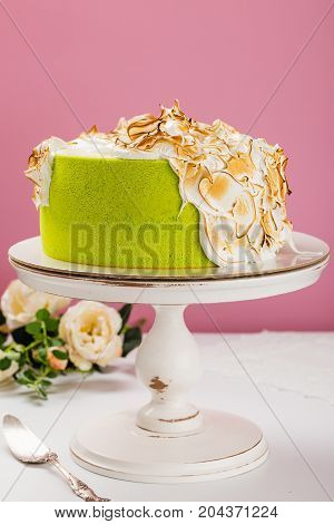 Green Cake Decorated With Burned Meringue