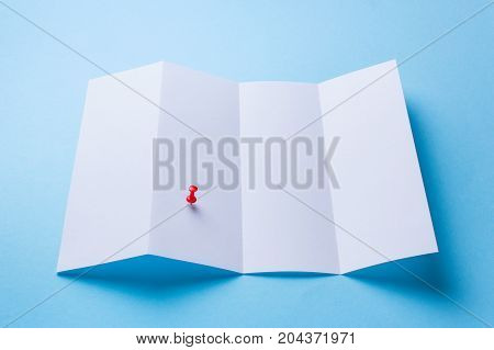 Map with red pin or Leaflet blank Four-fold white paper brochure mockup on blue background