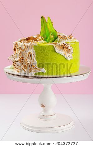 Green Cake Decorated With Burned Meringue And Colored Pear
