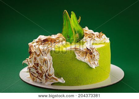 Birthday Cake With Burned Meringue And Colored Pear Slices On Green Background