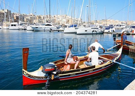 SENGLEA, MALTA - MARCH 31, 2017 - Passengers on board a traditional Maltese Dghajsa water taxi in the harbour with views towards Senglea waterfront Vittoriosa Malta Europe, March 31, 2017.