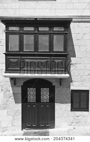 Building with traditional colorful maltese balcony and door in historical part of Valletta. Black and white picture