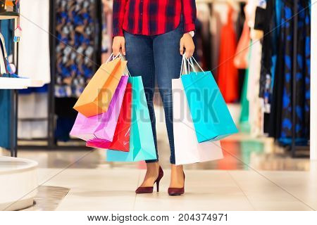 Young smiling attractive woman with a lot of color shopping bags in the fashion wear garments apparel store